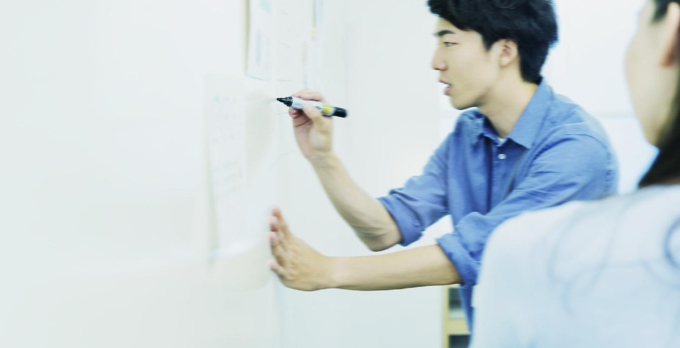 若者がホワイトボードに書き込んでいる画像